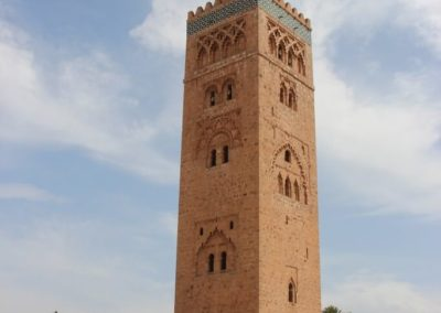 A large clock tower in front of Koutoubia Mosque