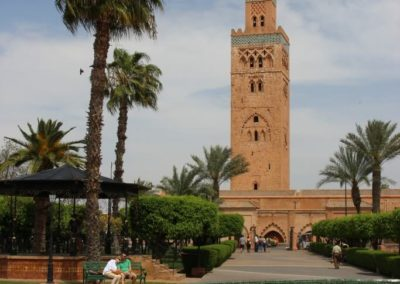 A large clock tower next to a palm tree with Koutoubia Mosque in the background