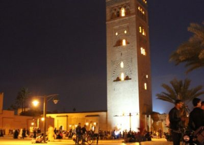 A clock tower lit up at night with Koutoubia Mosque in the background
