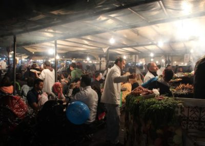 A group of people eating at a stand