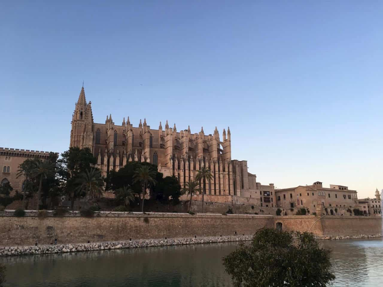 A castle surrounded by a body of water with Palma Cathedral in the background
