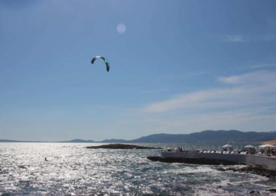 A man flying kite in a body of water