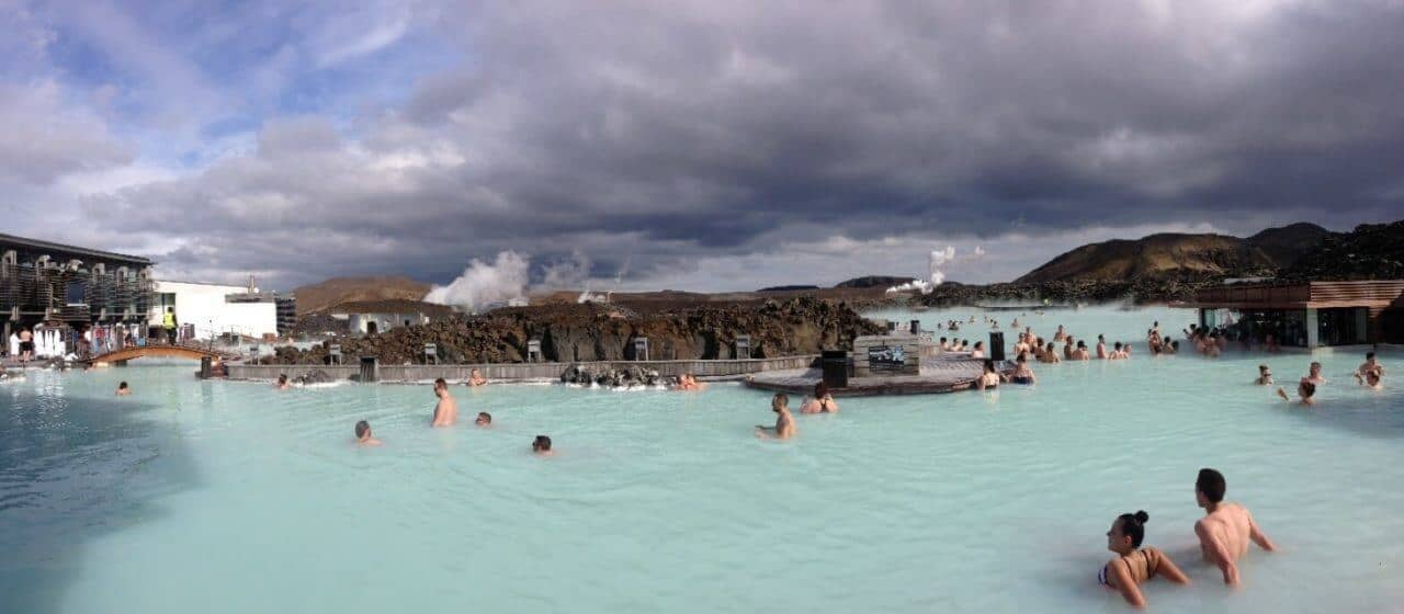 A group of people swimming in a body of water with Blue Lagoon in the background