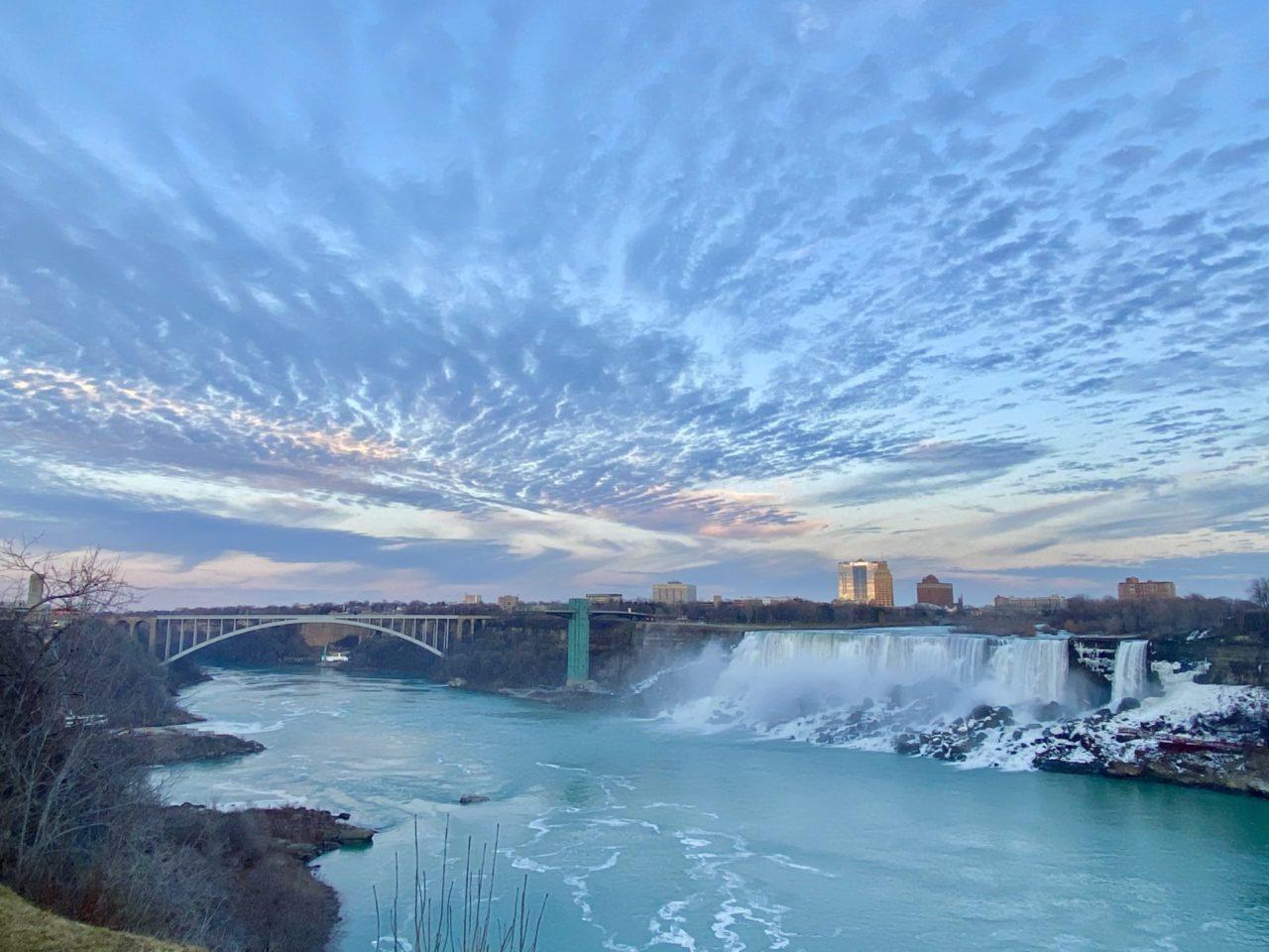 Eine Brücke neben Fluss und Wasserfällen