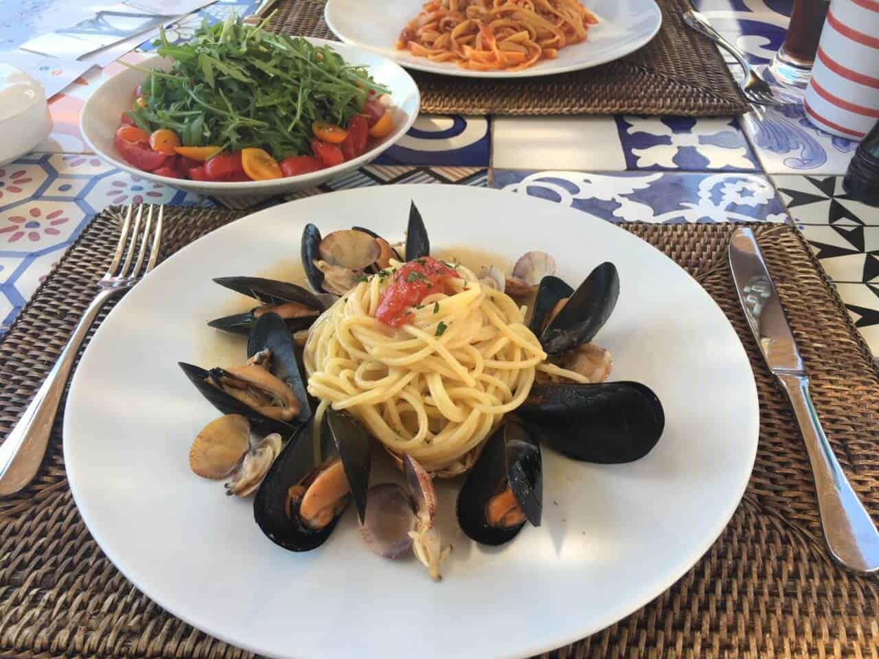 Teller mit Muscheln, Spaghetti und Salat