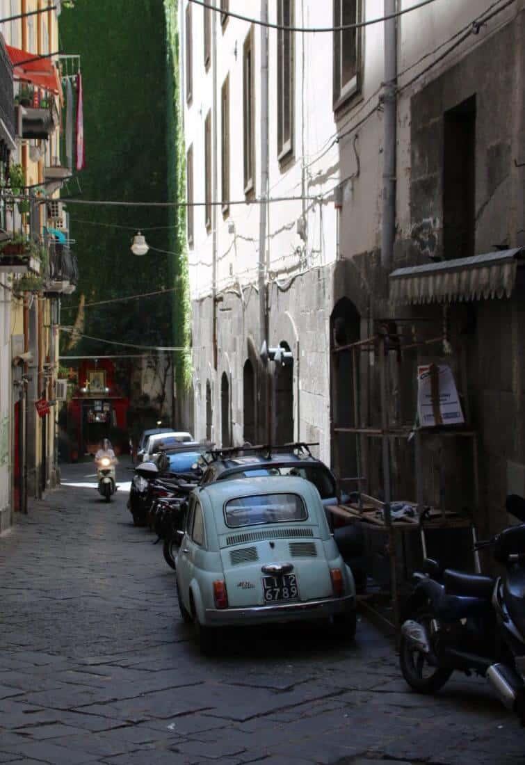 Gasse mit mehreren Autos und Motorroller