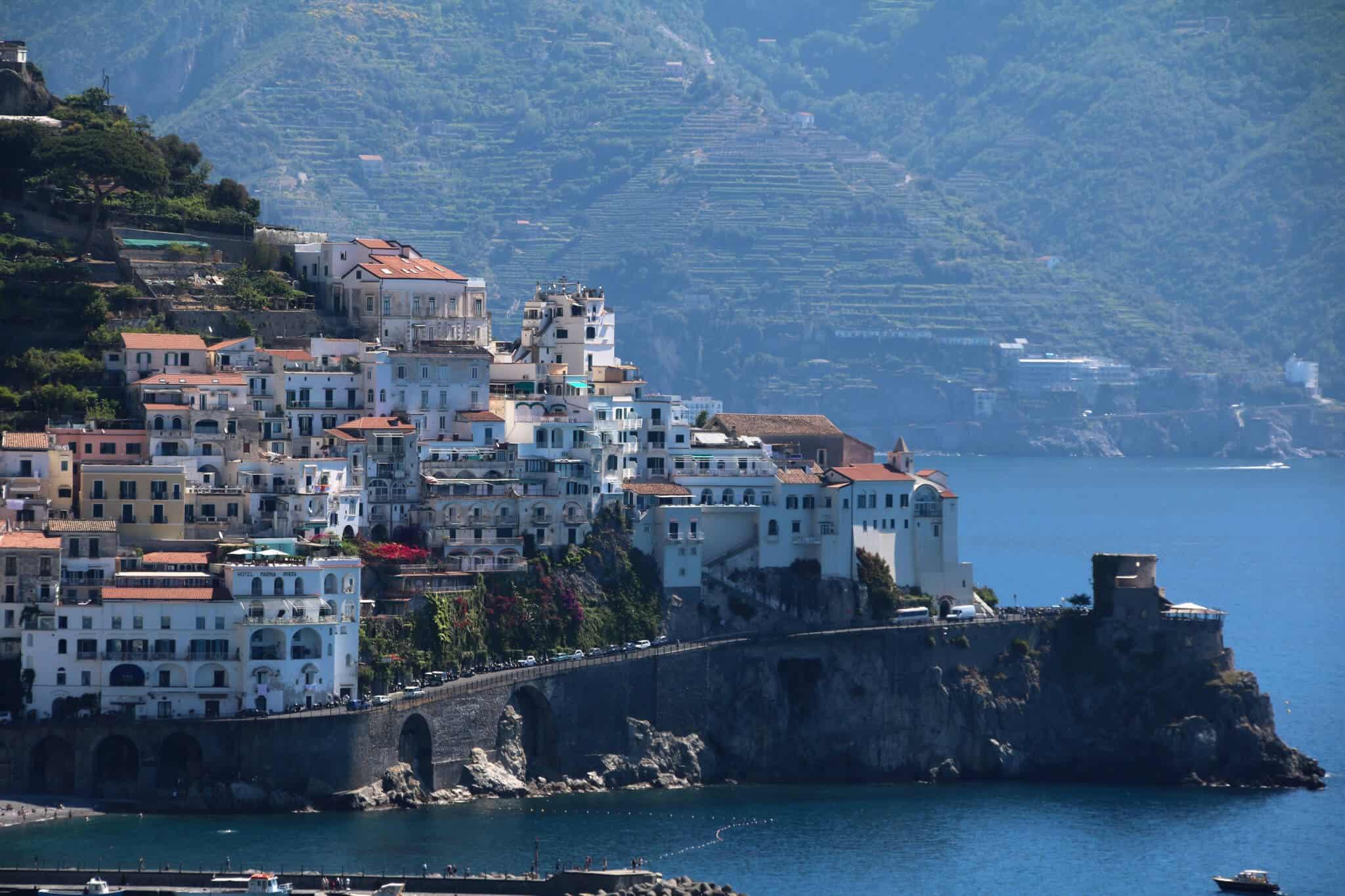 Küstenstraße mit Häusern, Meer und Gebirge