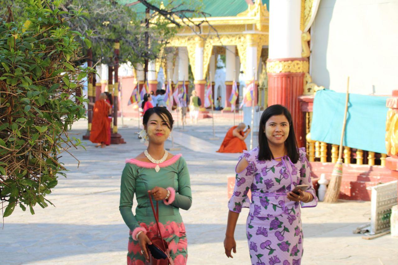 Zwei Frauen in bunten Kleidern und Strauch