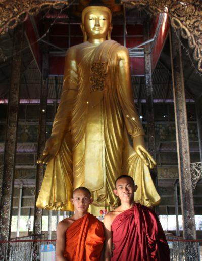 Stehender goldener Buddha und 2 Mönche in roten Kutten
