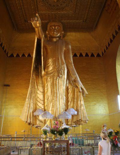 Stehender goldener Buddha und Blumen