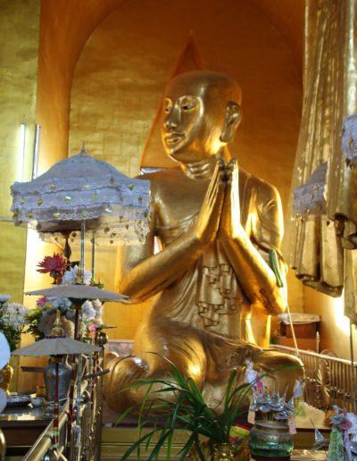 Sitzender goldener Buddha und Blumen