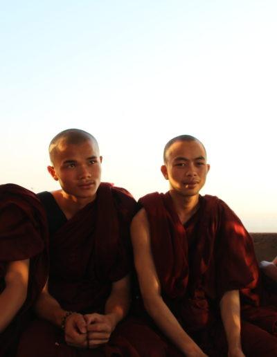 4 Mönche in roten Kutten auf Bank