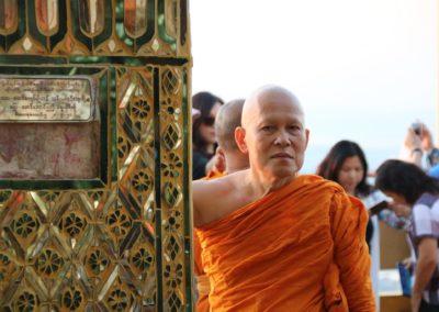 Mönch in oranger Kutte und bunte Hauswand
