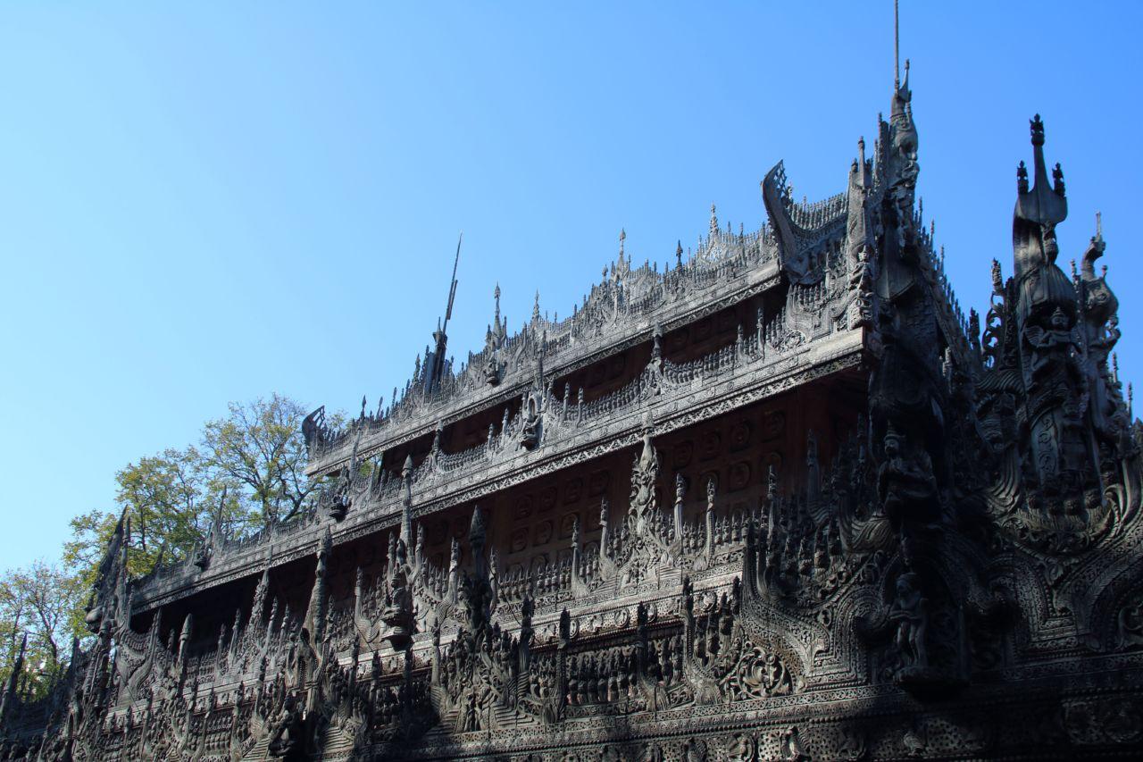 Pagode mit vielen Holz Figuren vor blauem Himmel