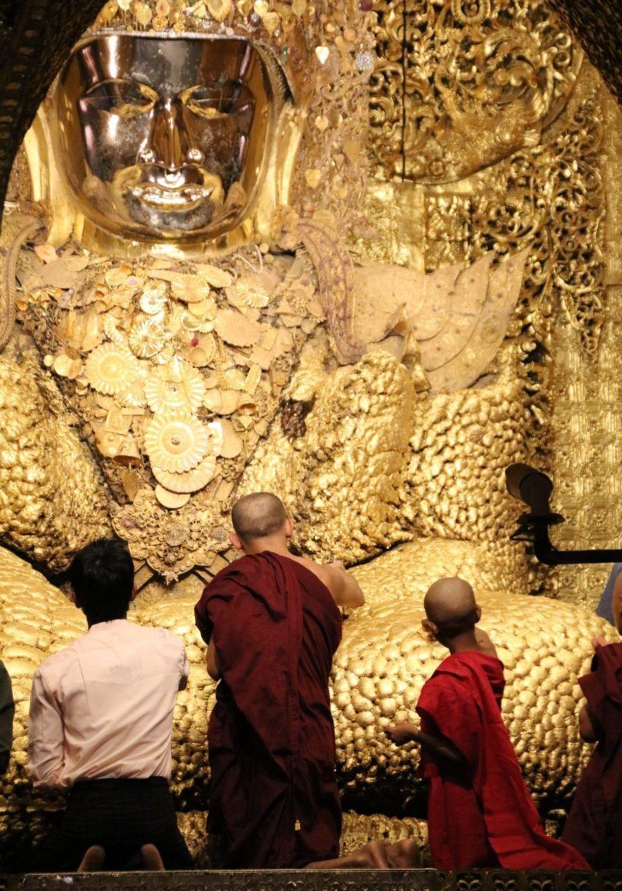 Männer von hinten vor goldener Buddha Statue