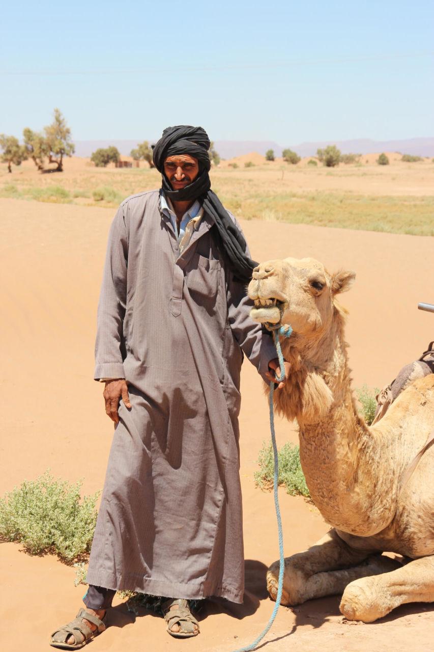 Mann in grauem Gewand mit Kamel