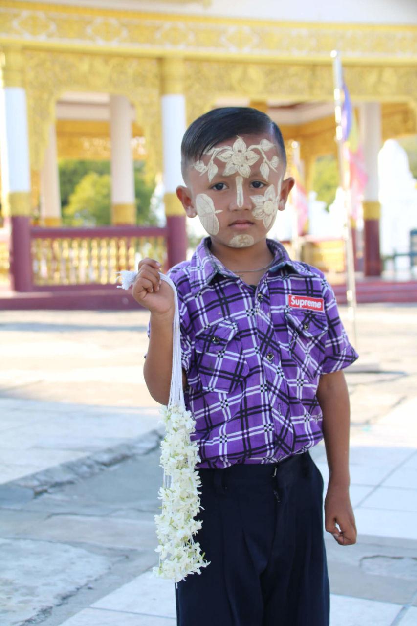 Kind mit Bemalung im Gesicht vor gelber Pagode