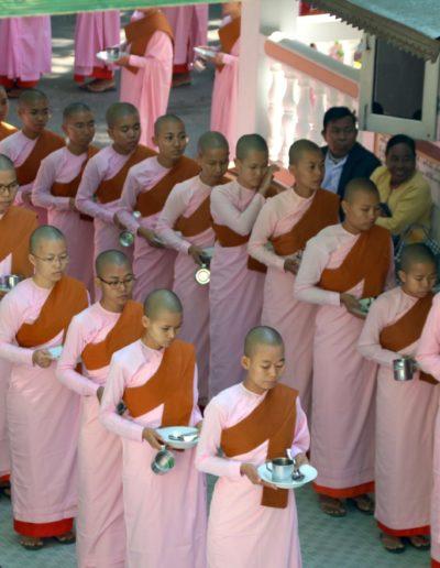 Gruppe von Frauen und Mädchen mit rosa Kleidern und Tellern in der Hand