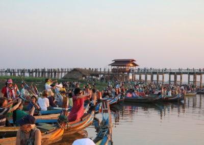 Menschen in Booten vor Holzbrücke