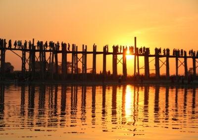 Menschen auf Holzbrücke in orangem Licht