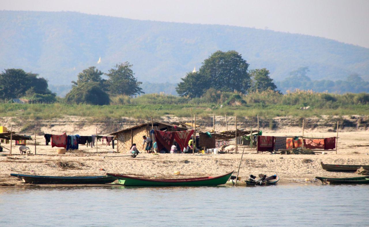 Boote, Zelte, Menschen, Bäume und Fluss