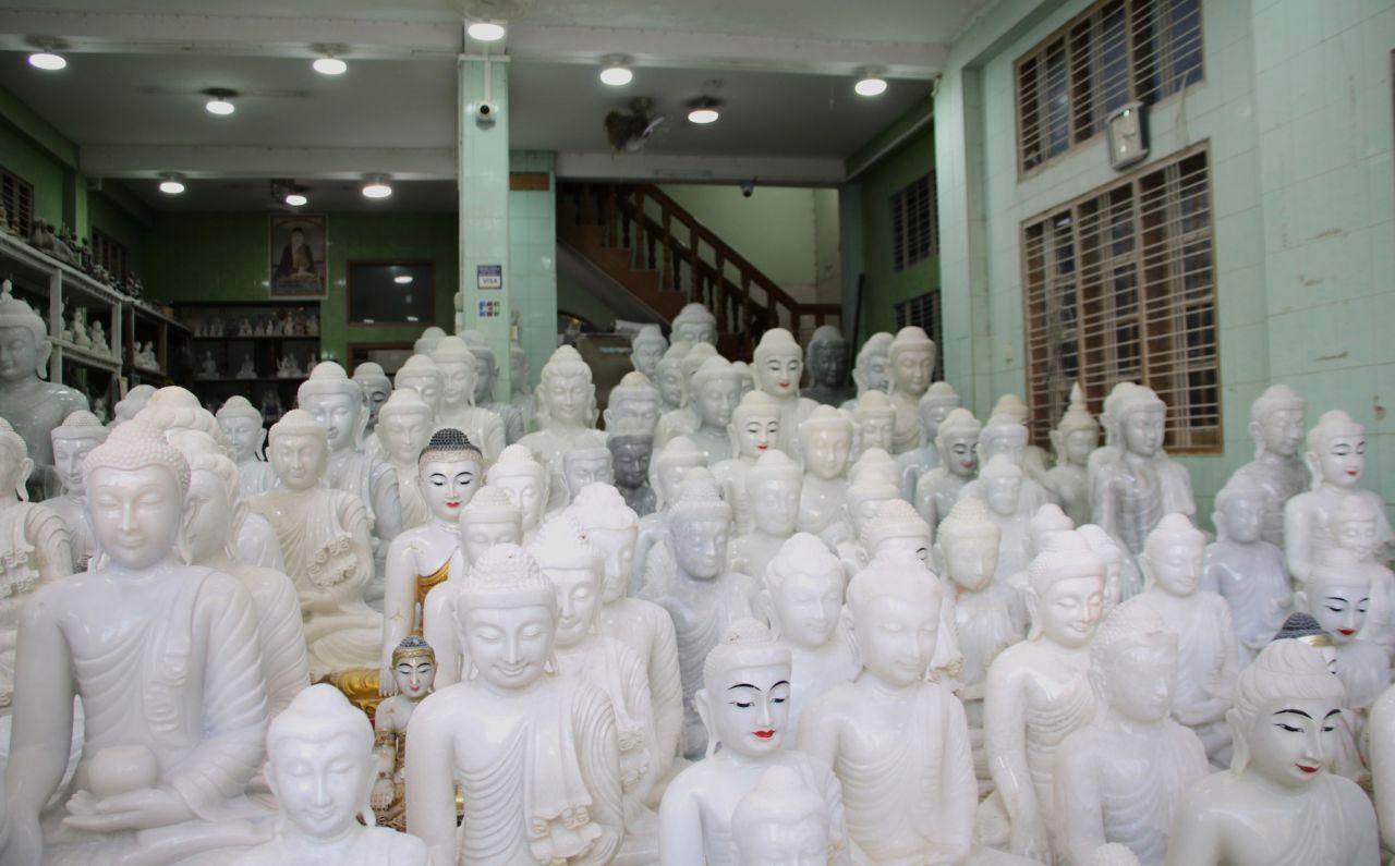 Weiße Buddhafiguren in einer Halle