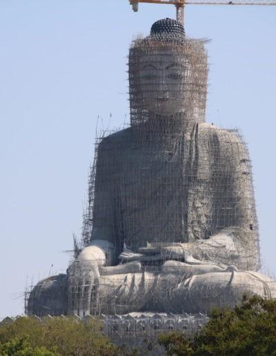 Gerüst um große graue Statue vor blauem Himmel