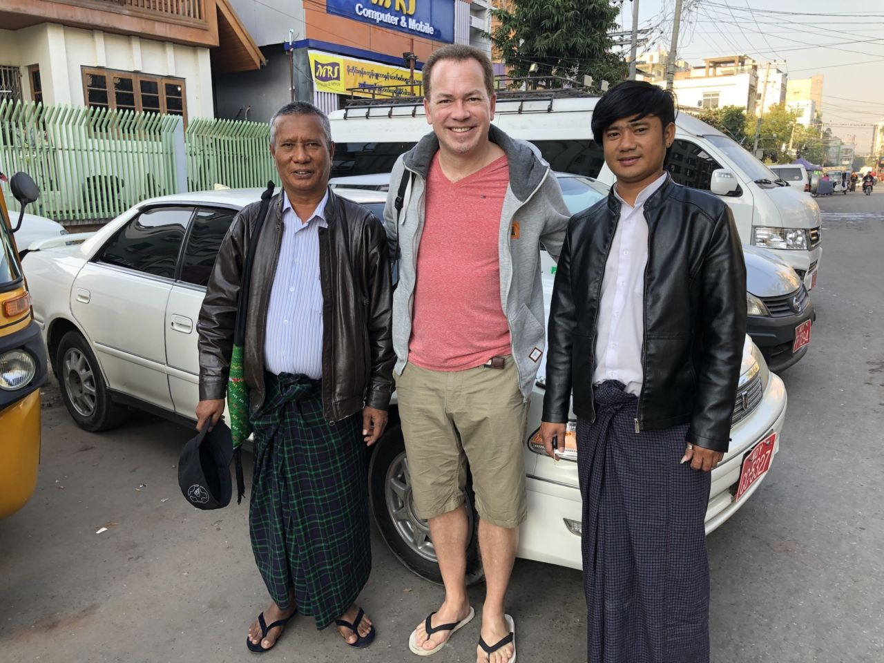 Drei Menschen vor drei Autos