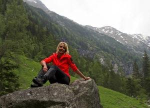 Frau mit roter Jacke sitzt auf Stein mit Gebirge im Hintergrund