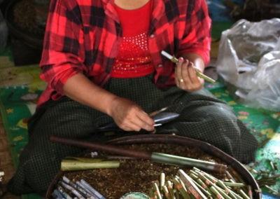 Frau mit roten Hemd vor Tisch der mit Zigarillos bedeckt ist