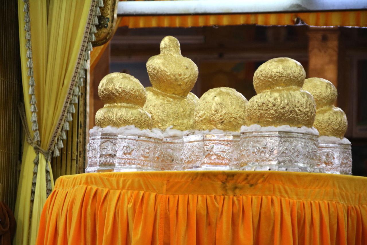 Buddha Figuren aus Gold auf einem Tisch mit oranger Decke