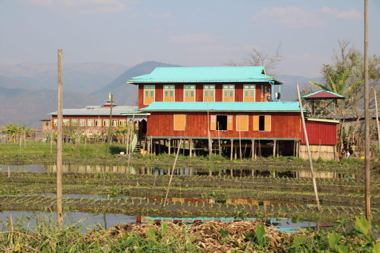 Haus auf Stelzen umgeben von Gärten im Wasser