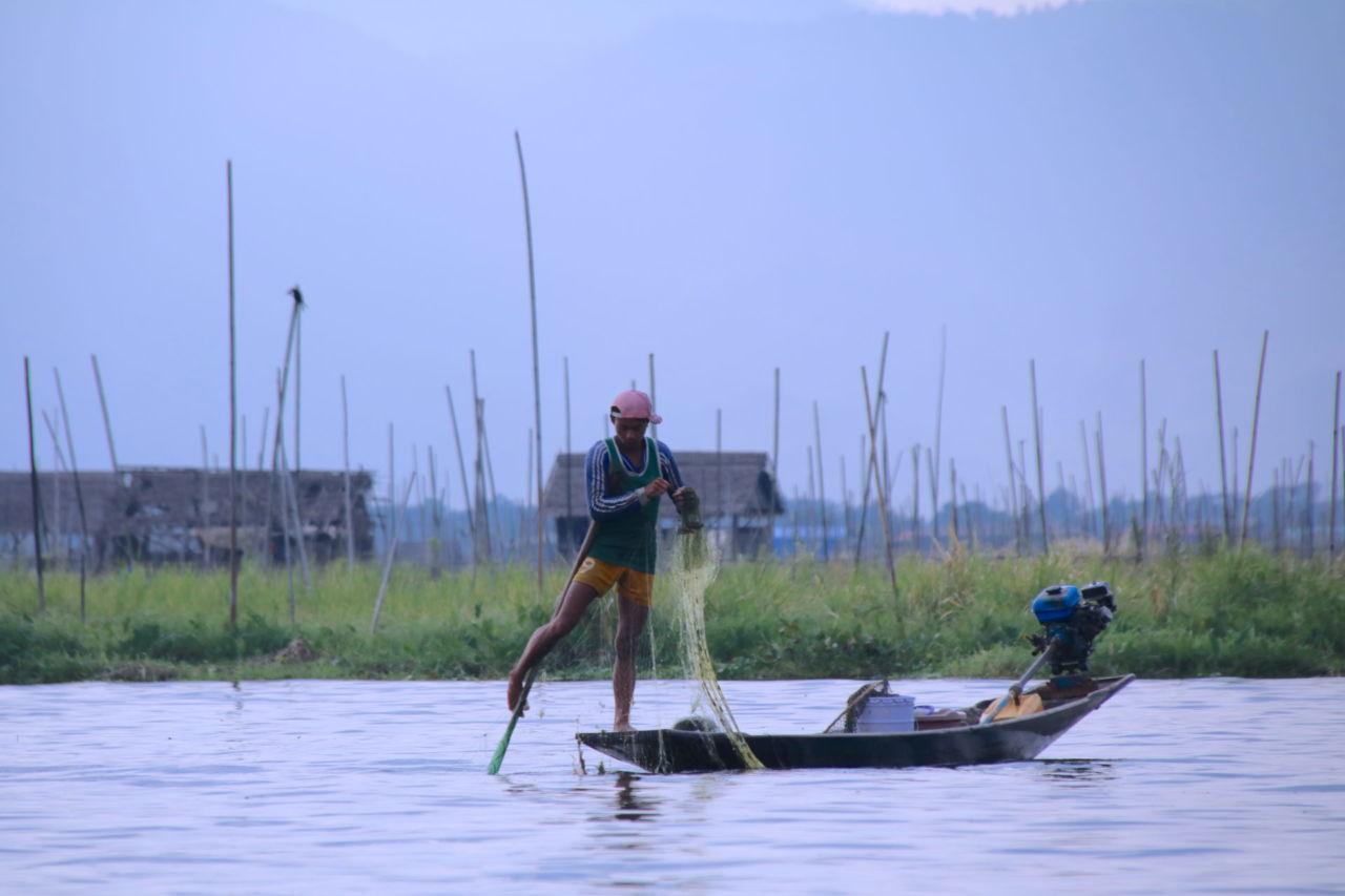 Ein Fischer mit einem Netz auf einem Boot auf dem Inlesee