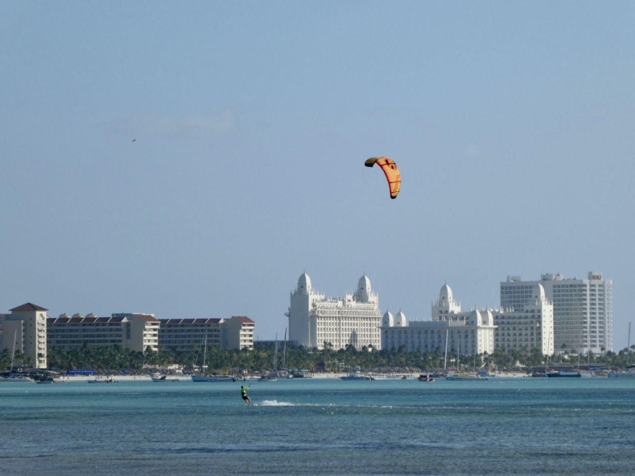 Ein Kitesurfer im Meer mit blauem Himmel und Hotels im Hintergrund