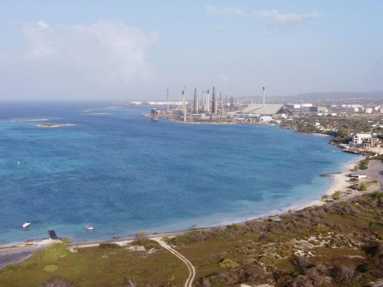 Eine Luftaufnahme eines Strandes mit Strand im Vordergrund und einer Fabrik im Hintergrund