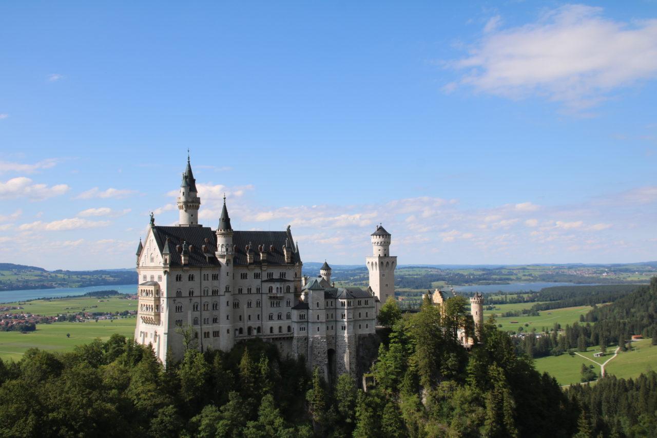Das Schloss Neuschwanstein mit Seen und Wiesn im Hintergrund