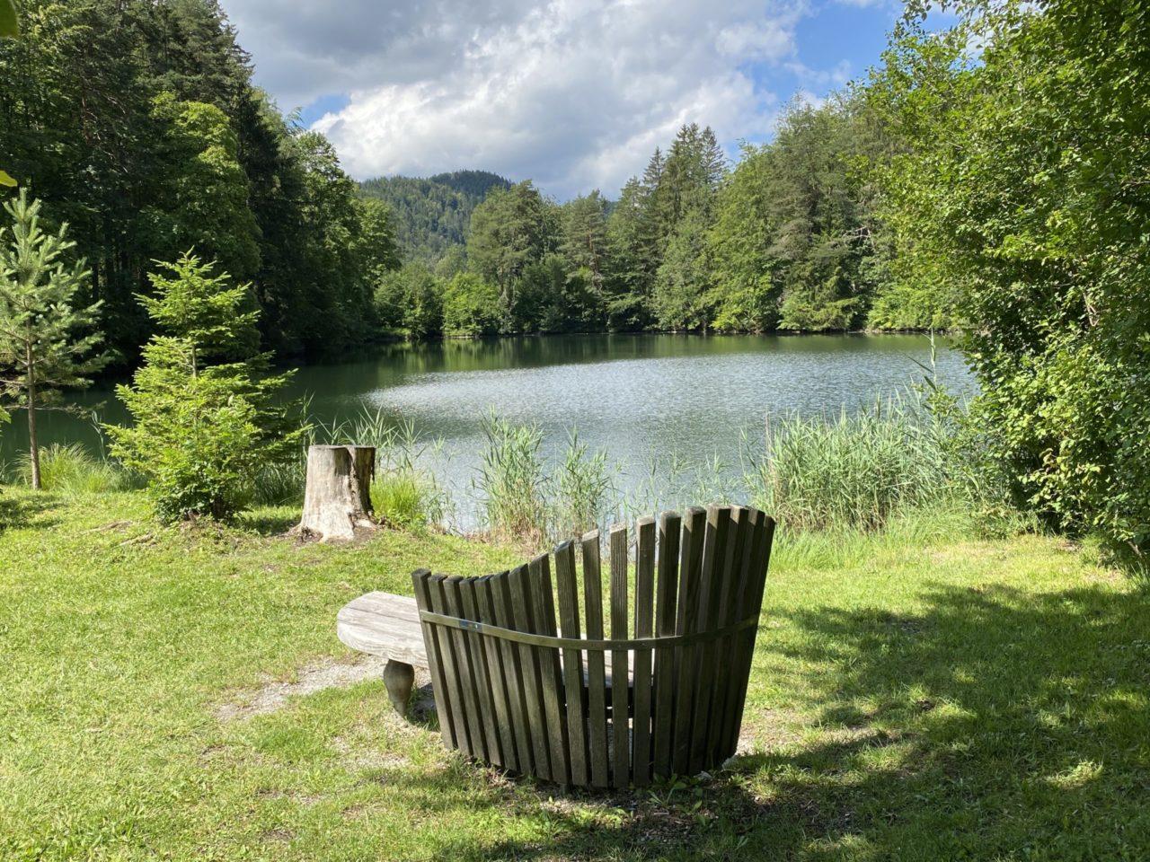 Eine Bank vor einem See im Wald