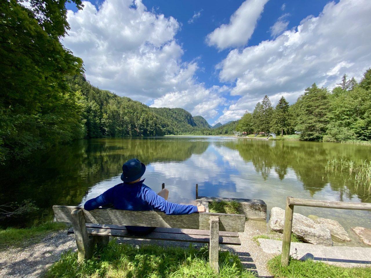 Ein Mann auf einer Bank vor einem See